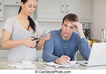 Disappointed woman cutting through a credit card with...