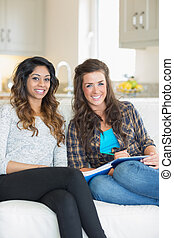 Two smiling girls sitting on a couch while writing on a...