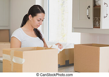 Woman unpacking in kitchen - Young woman unpacking in...