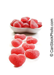 Red heart shaped sweets on white background