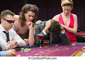 Woman comforting man losing at poker in casino