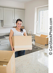 Smiling woman holding a moving box - Young smiling woman...