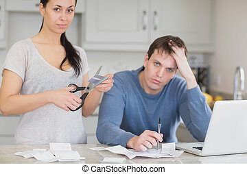 Disappointed couple in the kitchen cutting credit card and...