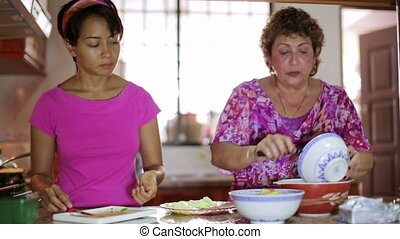 Mother daughter preparing meal together