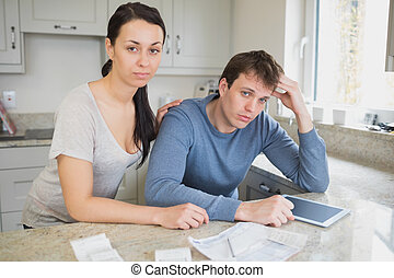 Couple calculating the finances - Two people in the kitchen...