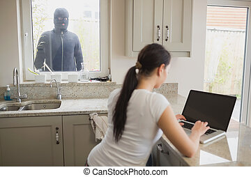 Woman being observed by burglar through window - Woman on...