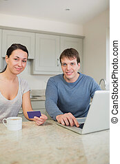 Couple sitting in the kitchen with a laptop and a credit...
