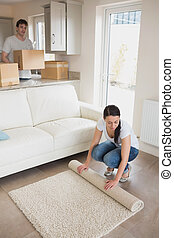 Woman laying out rug with man holding moving boxes in living...