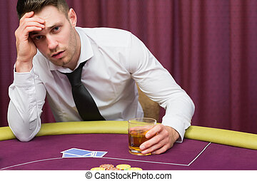 Man leaning on poker table drinking whiskey at casino
