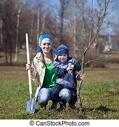 woman with her son planting tree outdoor - young woman with...