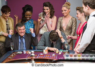 One man winning and one man losing at roulette table in...
