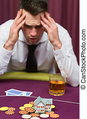 Man betting his house at poker game in casino