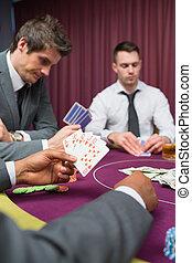 Man at poker table has royal flush