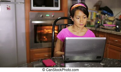 woman with laptop in kitchen