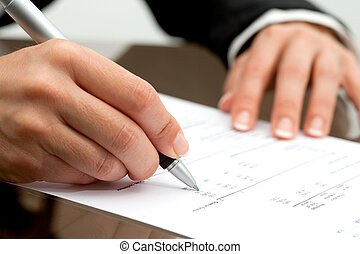 Female hand with pen pointing on accounting document.
