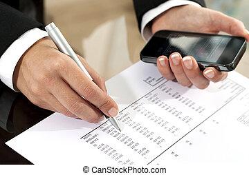 Female hands reviewing accounting document. - Close up of...