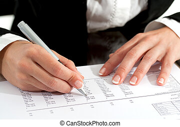 Female hands with pen reviewing document - Close up of...