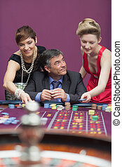 Woman placing bet for man at roulette
