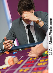 Man with cigar thinking at roulette table