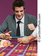 Man happy with his winnings at roulette table