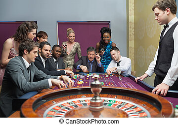 People placing bets on roulette table