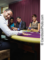 Smiling dealer at poker game in casino