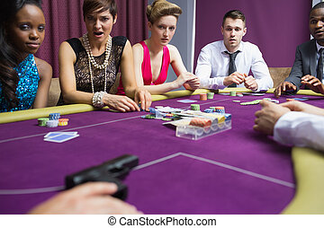 People looking scared at gun on table