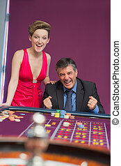 Man and woman cheering at roulette table
