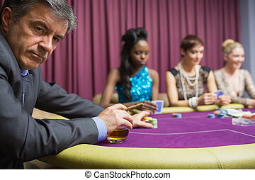 Man with whiskey looking angry at poker game
