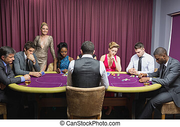 People sitting at the casino table with woman standing and...
