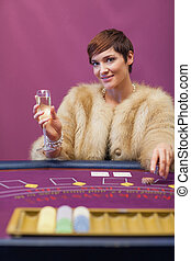 Woman drinking at table of a casino
