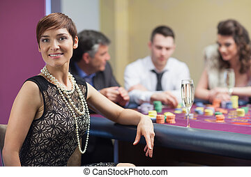 Smiling woman taking break from roulette with champagne in...