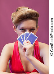 Woman in a casino holding cards before face