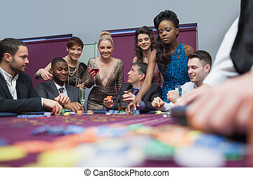 People standing and sitting at the table enjoying roulette