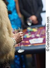 Woman in fur coat with champagne glass at roulette table