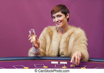 Woman with champagne at poker table in casino
