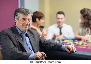 Man with cigar taking break from roulette table in casino