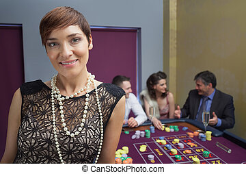 Woman smiling and standing at roulette table