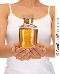 female hands with oil bottle - bright picture of female...