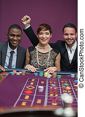 Three happy people at roulette table
