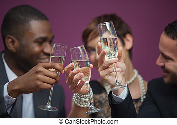 Three people toasting and celebrating in a casino while...