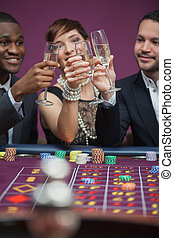 Three people toasting at roulette table