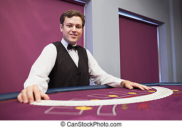 Smiling dealer with spread deck of cards at poker table
