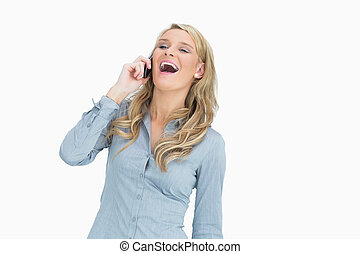 Woman laughing while calling with her mobile phone