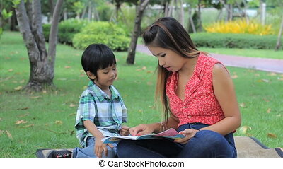 Asian Boy Learning How To Read - A pretty Thai mother...