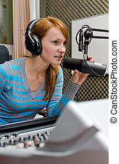 Portrait of female dj working in front of a microphone on...