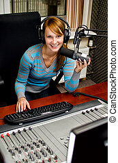 Portrait of female dj working in front of a microphone on the radio