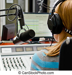 Rear view of female dj working in front of a microphone on...