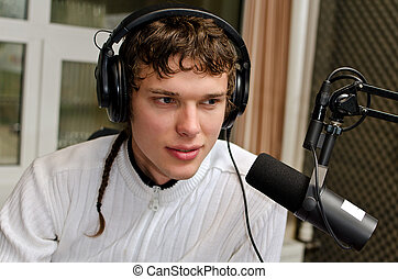Portrait of male dj working in front of a microphone on the radio