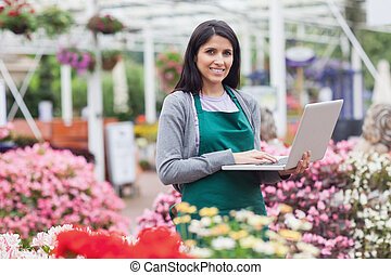 Woman using laptop in the garden center while smiling